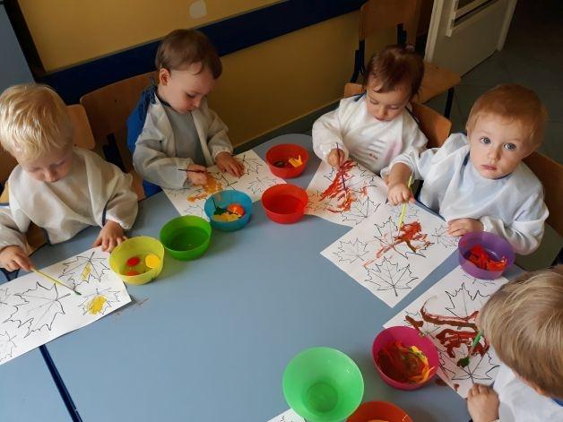 dzieci malują liście farbkami, każde dziecko ma swój szablon
