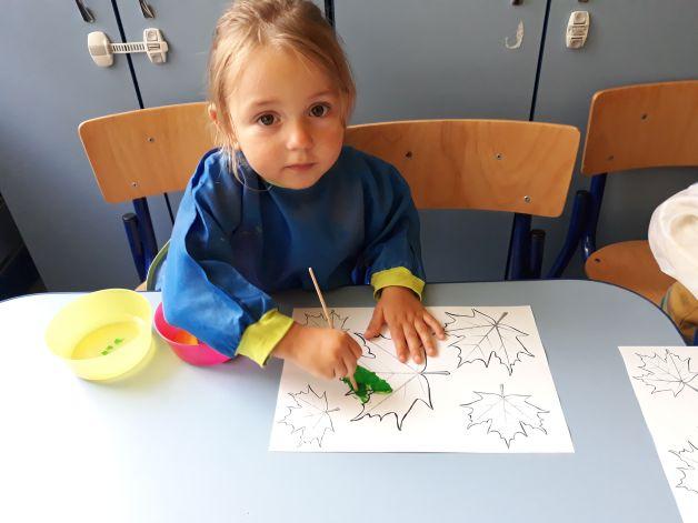 dziewczynka maluje liść na zielono