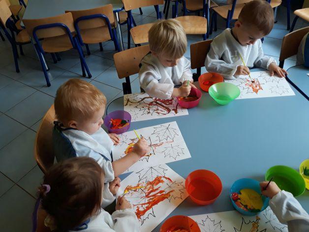 dzieci siedzą przy stole, malują liście