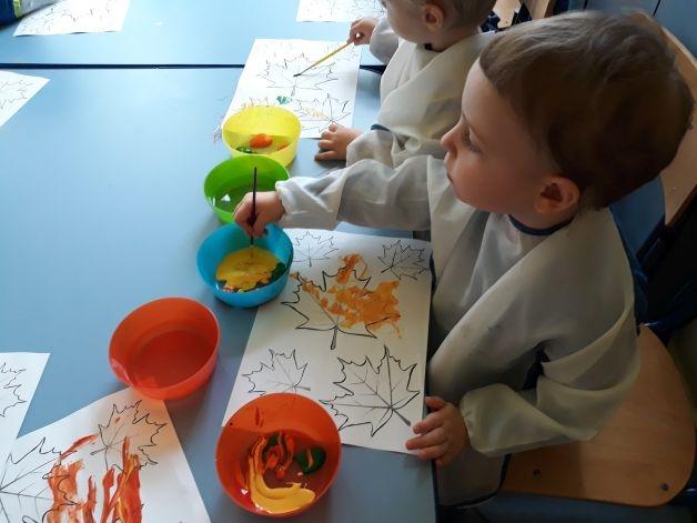 chłopiec maluje liść na żółto