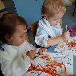 Dzieci farbami malują jesienne liście