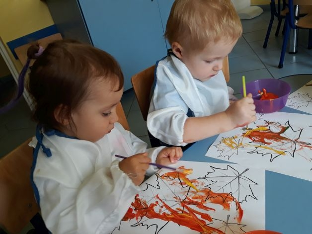 dwójka dzieci siedzi maluje liście