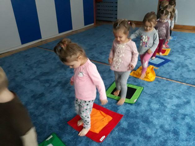 dzieci aktywnie uczestnicząw zajęciach. kilkoro dzieci idzie po ścieżce sensorycznej. Ścieżka to kolorowe kwadraty położone na podłodze