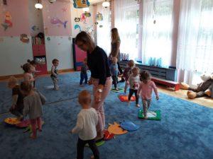 dzieci z Paniami chodzą dookoła po ścieżce sensorycznej