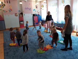 dzieci chodzą po przygotowanych szablonach położonych na podłodze.