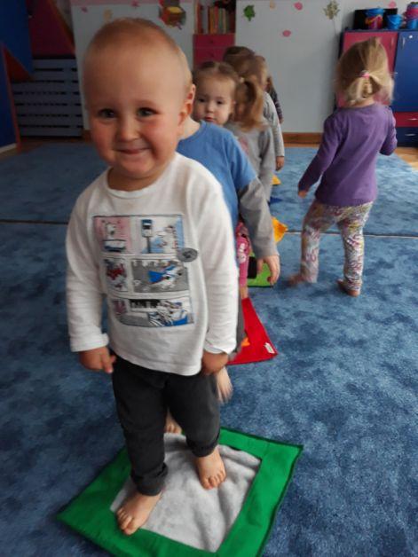chłopiec w pierwszym kadrze stoi na materiale w kształcie kwadratu, za nim idą inne dzieci