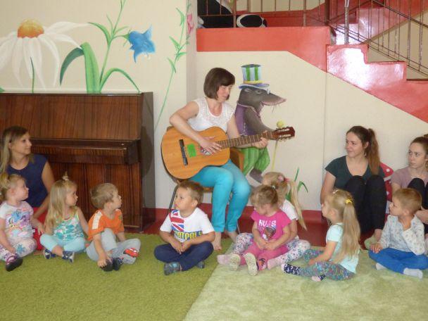 Pani gra na gitarze i śpiewa dzieciom