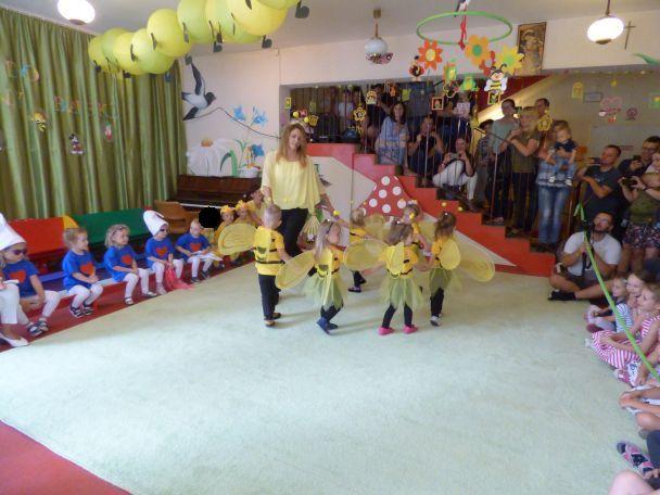dzieci w przebraniach pszczółek tańczą w kółku, rodzice oglądają przedstawienie